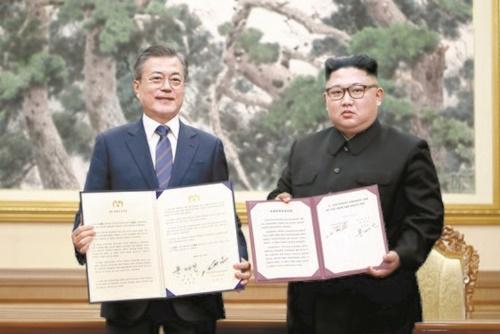 韓国の文在寅大統領(左)と北朝鮮の金正恩国務委員長(右)が昨年9月19日午前、平壌百花園迎賓館で平壌共同宣言文に署名した後、合意書を開いて取材陣に見せている。(写真=平壌写真共同取材団)