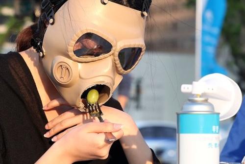 14日、ソウル光化門広場で開かれた「粒子状物質の中のダイニング」行事で、参加者が防毒マスクをかぶって食事をする姿を演出している。