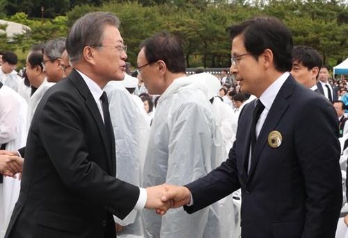 韓国の文在寅大統領(左)が18日午前、光州北区雲亭洞にある国立5・18民主墓地で開かれた第39周年5・18民主化運動記念式に参加し、野党「自由韓国党」の黄教安代表と握手している。(写真=青瓦台写真記者団)