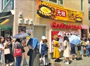 東京新大久保通りにある飲食店「クプネチキン(Goobne)」の前に日本人が「チーズタッカルビ」を食べるために列を作っている。