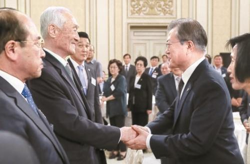4日、青瓦台で開かれた国家有功者および報勲家族を招いた昼食会で、韓国の文在寅大統領が6・25参戦有功者会のパク・ヒモ会長と挨拶している。(写真=青瓦台写真記者団)