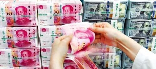 米中貿易対立後に韓国の人民元建て預金口座から資金が急速に抜けている。人民元の価値に対する不安が大きくなったためだ。KEBハナ銀行の行員が10日、ソウル・乙支路本店の偽変造対応センターで人民元をチェックしている。