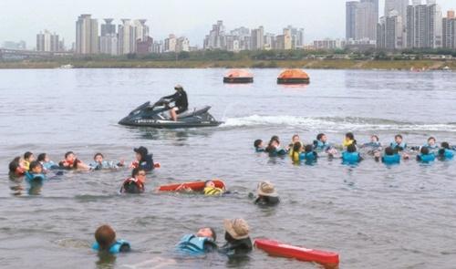 ソウルS小学校の児童が今月14日、漢江(ハンガン)でライフジャケットを着て生存水泳教育を受けている。
