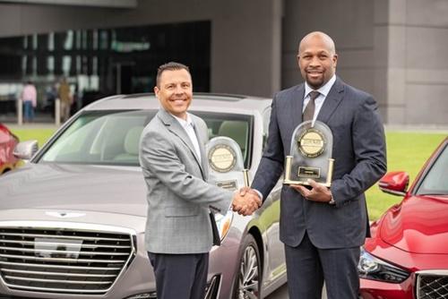 ジェネシス米総括のアーウィン・ラファエル氏が19日、J.Dパワーのマイケル・バッタリア副社長から最高品質賞を受けている。(写真=現代自動車グループ)