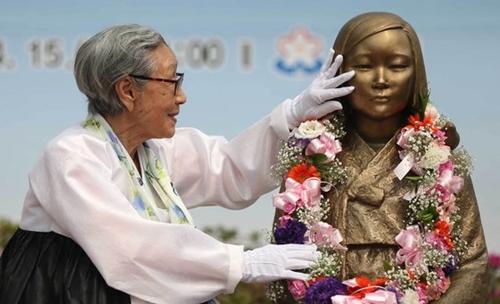 献花後に少女像に触れている慰安婦被害者の金福童さん。(写真=中央フォト)