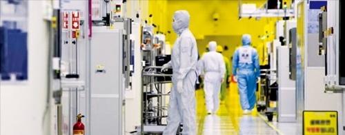 サムスン電子の職員が京畿道華城キャンパスの半導体生産ラインクリーンルームで半導体装備を点検している。(サムスン電子提供)