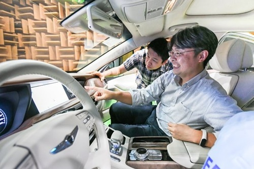 チュ・ギョウン現代・起亜車インフォテイメントセンター長(右)が先月24日、京畿道華城のナムヤン研究所で自動車用インフォテイメントシステムをテストしている。[写真 現代自動車グループ]