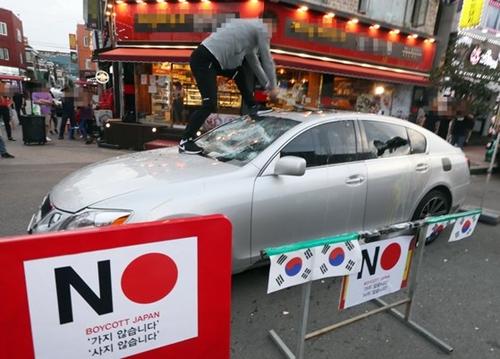 仁川市南洞区で行われた「日本経済報復糾弾不買運動宣言行事」で日本車レクサスをたたきつぶす市民[中央フォト]