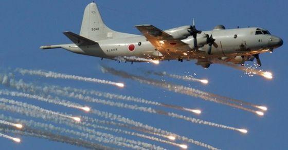 海上自衛隊所属P-3C哨戒機が赤外線誘導ミサイルを避けるためのフレアを放出しながら飛行している。[中央フォト]