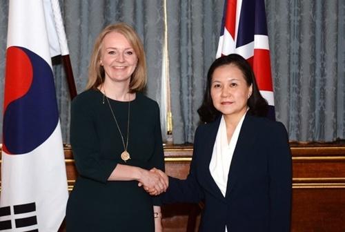 兪明希(ユ・ミョンヒ)産業通商資源部通商交渉本部長(右)とエリザベス・トラス英国際貿易相が22日午前、英ロンドン外務省会議室で韓英自由貿易協定に正式署名した。[写真 産業通商資源部]