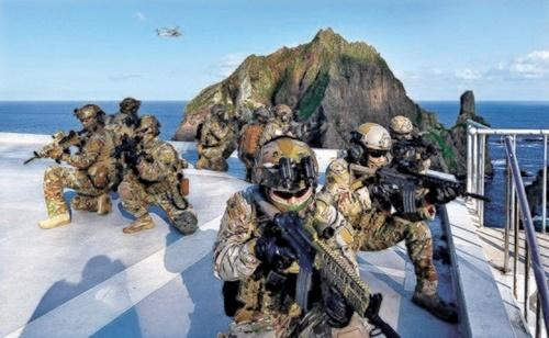 「韓日軍事情報包括保護協定(GSOMIA)」終了宣言3日目である25日、韓国軍が独島防御訓練に突入した。史上初めてイージス艦「世宗大王」と陸軍特殊戦司令部が参加した.訓練初日、独島東島ヘリコプーター着陸地に着陸した海軍特殊戦旅団(UDT/SEAL)隊員が作戦を展開している。[写真 韓国海軍]