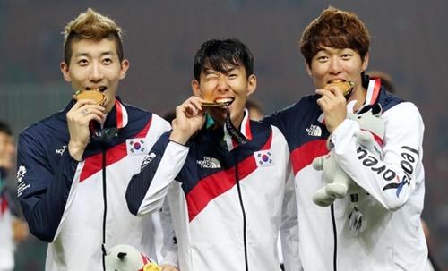 2018ジャカルタ・パレンバン・アジア競技大会サッカー決勝の授賞式後、趙賢祐、孫興民、黄儀助が金メダルを噛んでいる。