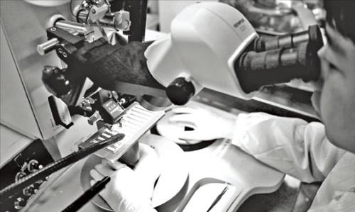 韓国光技術院の研究員が電子顕微鏡で光ファイバー素材を観察している。 [写真 韓国光技術院提供]