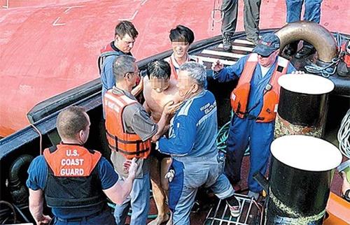 9日(現地時間)、米国沿岸警備隊は米東部沖で転覆した現代グロービス所属の貨物船「ゴールデン・レイ」の中に取り残されていた韓国人船員4人全員を救助した。最後に救助された韓国人船員(中央)が海岸警備隊の船舶に移動している。[写真 米沿岸警備隊]