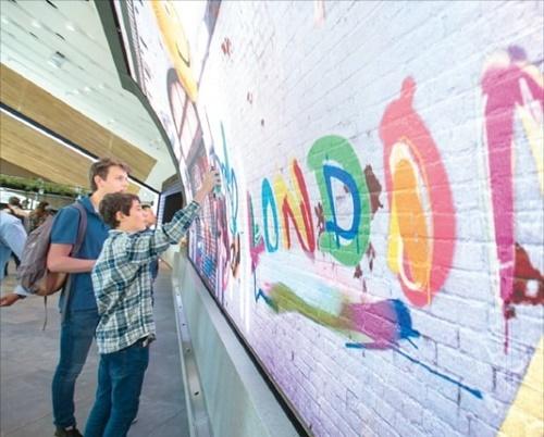 8日にサムスンキングスクロスを訪問したロンドン市民が「ギャラクシーグラフティー」を体験している。[写真 サムスン電子]