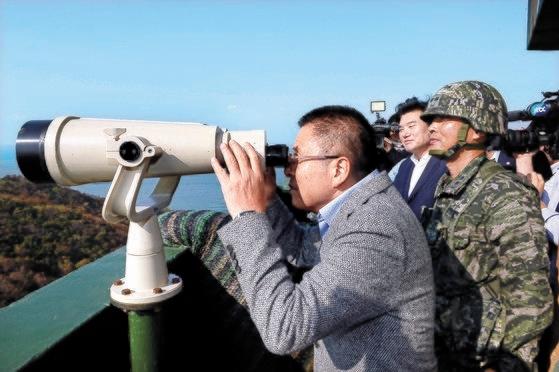 自由韓国党の黄教安代表が24日、仁川市江華郡海兵第2師団マル島小哨を訪問し、望遠鏡でハムバク島を眺めた。黄代表は北朝鮮の軍施設について「南北軍事合意に違反する」とし「今からでも北が施設を撤去する措置が必要だが、今の政府は放置している」と批判した。[写真 国会写真記者団]