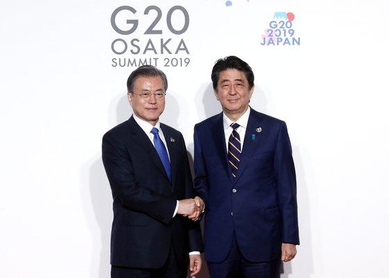 文在寅大統領(左)が6月、インテックス大阪で開かれたG20首脳会議の公式歓迎式で議長国である日本の安倍晋三首相と記念撮影を行っている。[写真 青瓦台写真記者団]