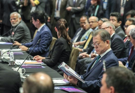 ASEAN+3首脳会議に出席するためシンガポールを訪問中の文在寅大統領(写真右)が15日午後、サンテック国際会議展示場で開かれた東アジア首脳会議に参加し、シンガポールのリー・シェンロン首相の冒頭発言を聞いている。2席隣に安倍晋三首相が見える。[写真 青瓦台写真記者団]