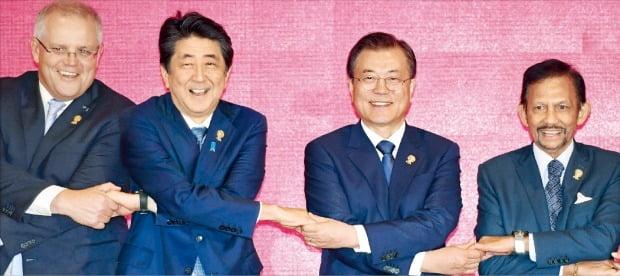 文在寅大統領が4日、タイ・バンコクのインパクトフォーラムで開催された東アジア地域包括的経済連携(RCEP)首脳会議で、安倍晋三首相と手を取り合って記念撮影している。左側からモリソン豪州首相、安倍首相、文大統領、ボルキア・ブルネイ国王。 バンコク=ホ・ムンチャン記者