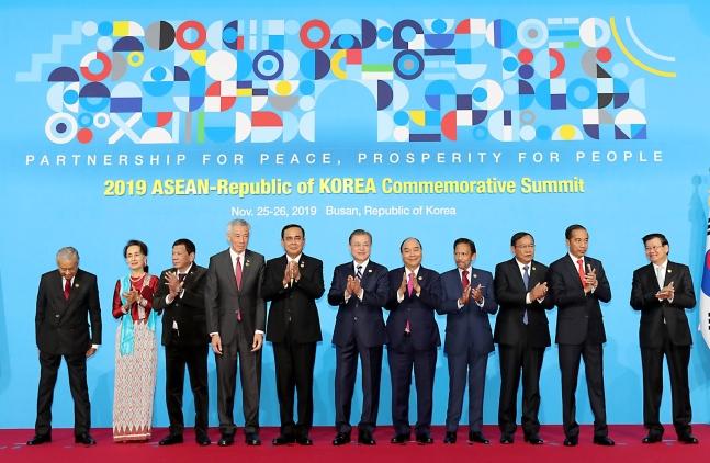 文在寅大統領が11月26日午前に釜山のBEXCOで開かれた2019韓国・ASEAN特別首脳会議で出席者と記念撮影をした後拍手している。左からマレー氏はのマハティール首相、ミャンマーのスー・チー国家顧問、フィリピンのドゥテルテ大統領、シンガポールのリー・シェンロン首相、タイのプラユット首相、文大統領、ベトナムのフック首相、ブルネイのボルキア国王、カンボジアのプラック・ソコン副首相兼外相、インドネシアのジョコ大統領、ラオスのトンルン首相。[写真 2019韓国・ASEAN特別首脳会議]