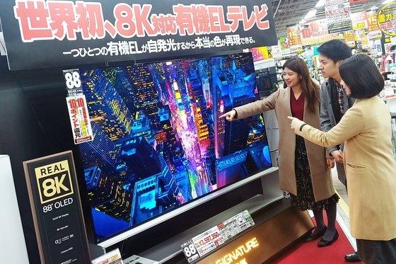東京秋葉原にあるヨドバシカメラのショップで客が「LGシグネチャー有機EL8K」の鮮明な8K解像度を体験している。[写真 LGエレクトロニクス]
