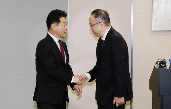 16日、都内にある経済産業省の会議室で、韓国側代表の李浩鉉・産業通商資源部貿易政策局長(左側)と日本側代表の飯田陽一・経済産業省貿易管理部長(右側)が握手している。[写真 韓国産業通商資源部]
