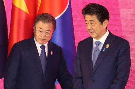 韓国の文在寅大統領(左)が先月4日、タイ・バンコクのインパクトフォーラムで開かれた第21回ASEANプラス3首脳会議の記念撮影のために安倍晋三首相と並んでいる。[写真 青瓦台写真記者団]
