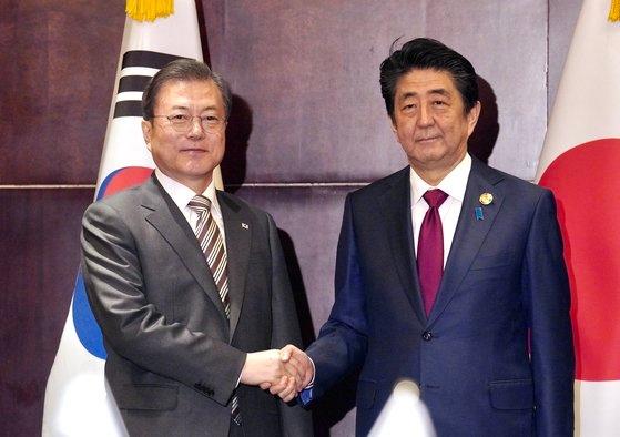 韓国の文在寅大統領が24日午後、中国四川省成都で韓日首脳会談の席で安倍晋三首相と会って握手をしている。[写真 青瓦台写真記者団]