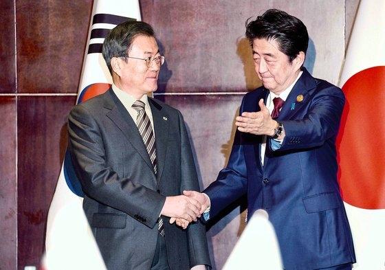 文在寅大統領が24日午後、中国四川省成都で安倍晋三首相と握手している。[青瓦台写真記者団]