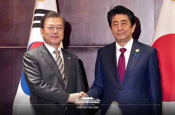 文在寅大統領と安倍首相が24日、中国四川省成都で韓日首脳会談の前に握手している。[写真 青瓦台]