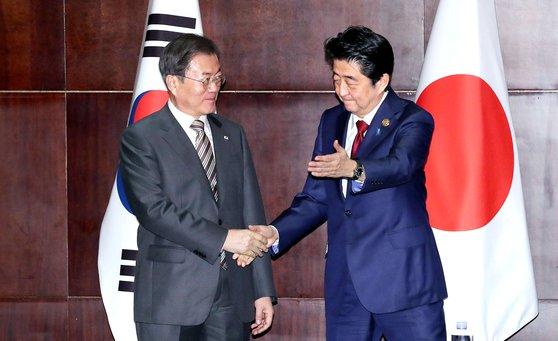 韓国の文在寅(ムン・ジェイン)大統領(左)と日本の安倍晋三首相が24日、中国四川省成都世紀城シャングリラホテルで開かれた首脳会談で握手をしている。[写真 青瓦台写真記者団]