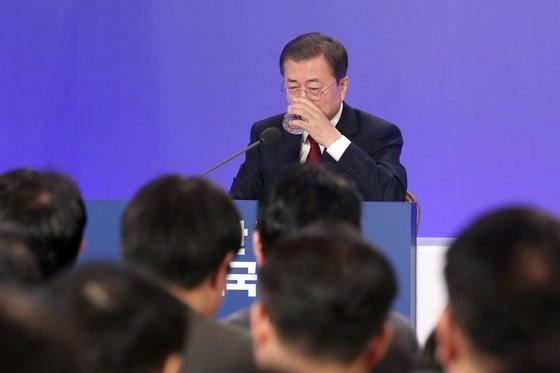 韓国の文在寅大統領が14日、青瓦台迎賓館で開かれた新年記者会見の途中で水を飲んでいる。[写真 青瓦台写真記者団]