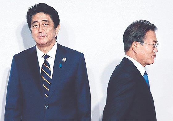 韓国の文在寅大統領(右)が2019年6月28日、大阪で開かれたG20(20カ国・地域)首脳会議の歓迎式で安倍晋三首相(左)と握手した後に移動している。[写真 青瓦台写真記者団]