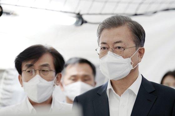 文在寅大統領が先月28日午前、新型コロナウイルス感染症の対応状況を点検するためにソウル中区国立中央医療院を訪問して総力対応を呼びかけた。文大統領が国立中央医療院の選別診療所控室でマスクを着用したまま報告を受けている。左はチョン・ギヒョン医療院長。[写真 青瓦台]