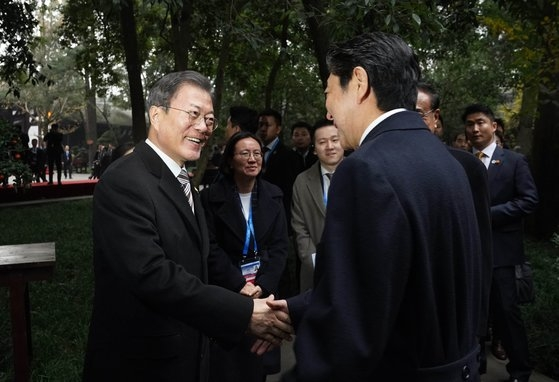 韓国の文在寅大統領と日本の安倍晋三首相、中国の李克強首相が昨年12月24日(現地時間)、中国四川省成都杜甫草堂で開かれた韓日中協力20周年記念除幕式に出席した。文大統領(左)が安倍首相と別れのあいさつをしている。[写真 青瓦台写真記者団]