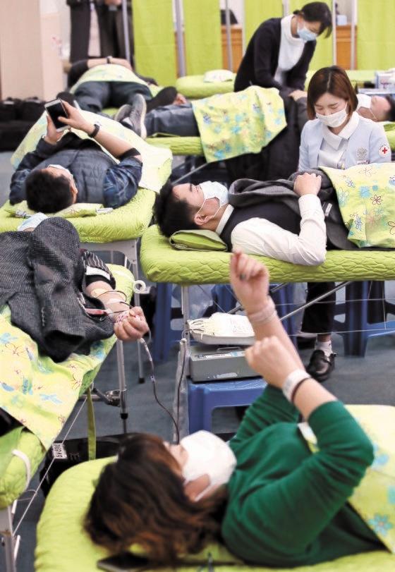 12日、献血人口が急減して大韓赤十字社の献血保有量が徐々に少なくなっている事態を受け、公務員が釜山市庁大会議室で集団献血をしている。