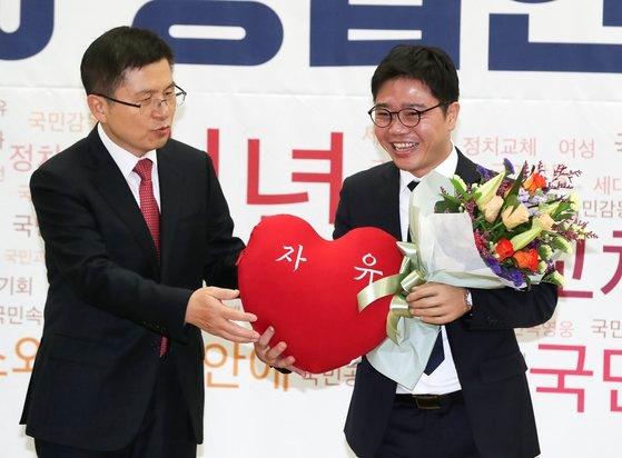 自由韓国党の黄教安(ファン・ギョアン)代表(左)が1月8日国会議員会館で開かれた「2020招聘人材歓迎式」で脱北者出身の人権運動家、チ・ソンホ氏に花束とクッションを渡している。