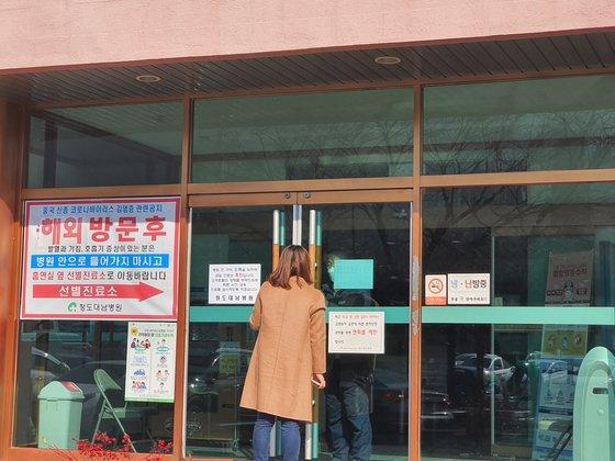 20日、慶尚北道清道郡清道テナム病院を訪れた訪問者が堅く閉じられたドアの隙間から病院関係者と話している。チン・チャンイル記者