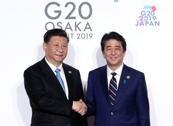 習近平中国国家主席(左)が昨年6月28日に大阪で開かれたG20首脳会議公式歓迎式で議長国の日本の安倍晋三首相とあいさつを交わしている。[写真 青瓦台写真記者団]