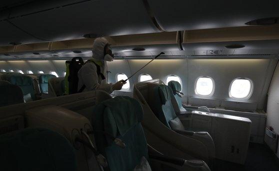 4日午後、仁川国際空港で防疫会社の職員がニューヨーク行き大韓航空機の消毒作業をしている。 キム・ソンリョン記者