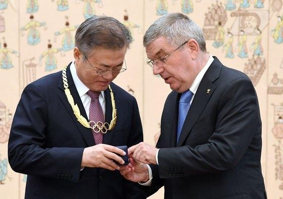 文在寅大統領(左)が2018年に青瓦台でIOCのバッハ会長から平昌五輪の開催成功など五輪に貢献した功労で勲章を受け取り、記念バッジについての説明を聞いている。[写真 青瓦台写真記者団]