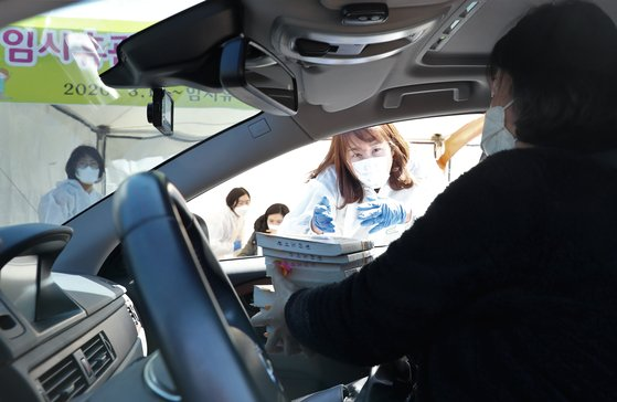 ある市民が11日、済州市漢拏図書館で「ブックドライブスルー」を利用して本を借りている。[写真 済州道]