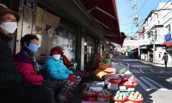 22日、ソウル弘恩洞(ホンウンドン)ポバント市場で、マスクを着用した店の女性が通行人を眺めている。 オ・ジョンテク記者