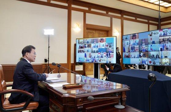 文在寅大統領が26日、青瓦台執務室で分割された大型モニター画面に登場したG20首脳らを見ながら「G20特別テレビ首脳会議」に参加している。[写真 青瓦台写真記者団]
