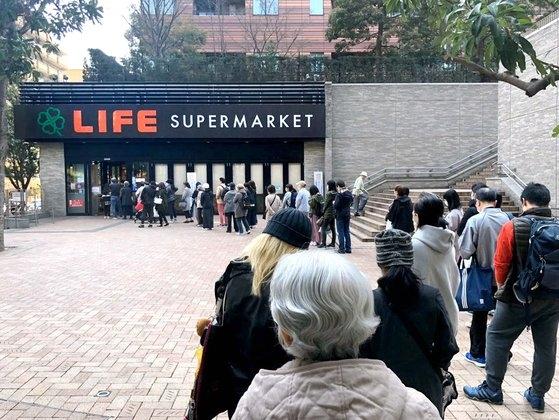 25日午前、東京目黒区のあるスーパーマーケットの前に食料品を買おうとする市民が長い列をつくっている。ソ・スンウク特派員