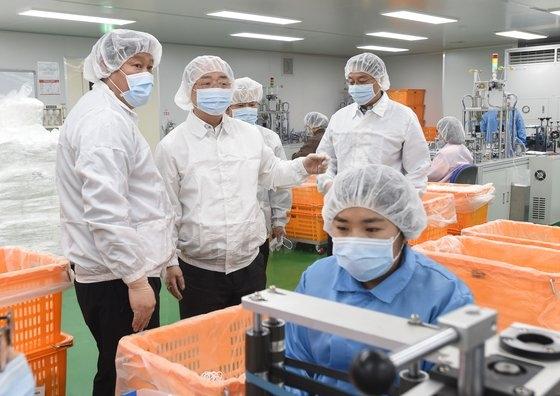 洪楠基副首相兼企画財政部長官(左から2人目)が先月、京畿道安城のマスクメーカーのKMを訪問し、生産現場を視察して関係者から説明を聞いている。[写真 企画財政部]
