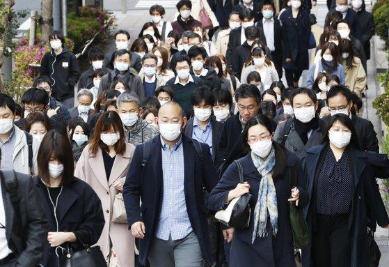 新型コロナウイルスの感染拡大で緊急事態宣言の対象地域が日本全国に拡大した中、17日午前、東京都中央区でマスクを着用した会社員が出勤している。