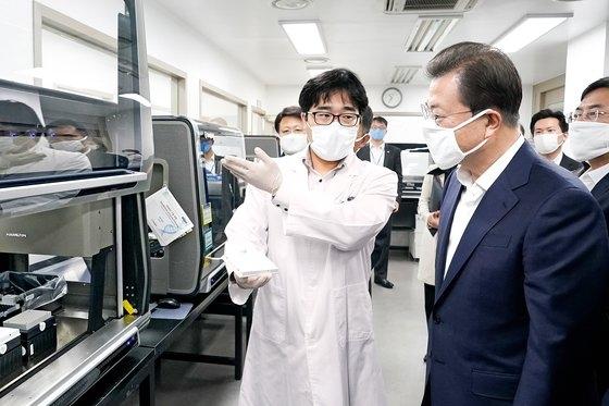 文在寅(ムン・ジェイン)大統領が3月25日、ソウル松坡区(ソンパグ)の新型コロナ感染症診断試薬緊急使用承認企業研究室を訪問して関係者から説明を聞いている。文大統領は「防疫は皆さんから始まる」と激励した。[写真 青瓦台写真記者団]