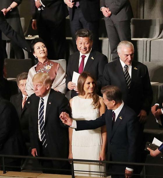 2017年にドイツのハンブルグで開かれたG20首脳会議文化公演を終えトランプ大統領が文在寅大統領の手を握っている。後方にいる習近平中国国家主席が見つめている。[写真 青瓦台]