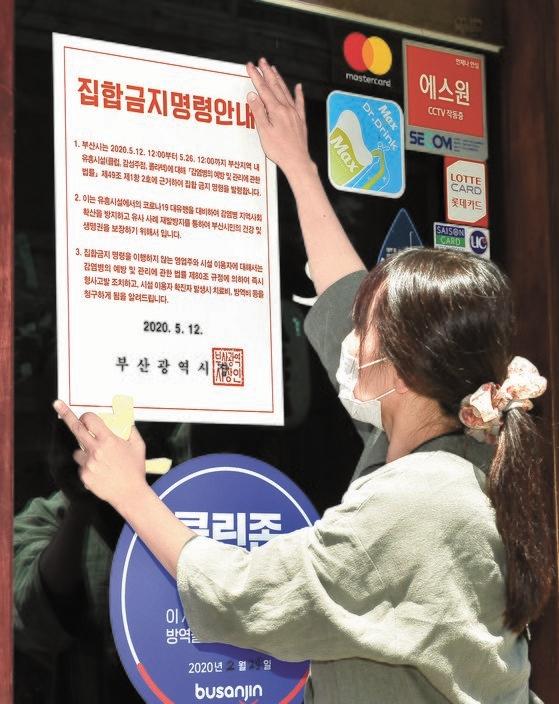 釜山市公務員が西面(ソミョン)一帯の遊興施設に集合禁止命令書を貼り付けている。釜山市は26日までに計71カ所の遊興施設に集合禁止命令を発令した。ソン・ボングン記者